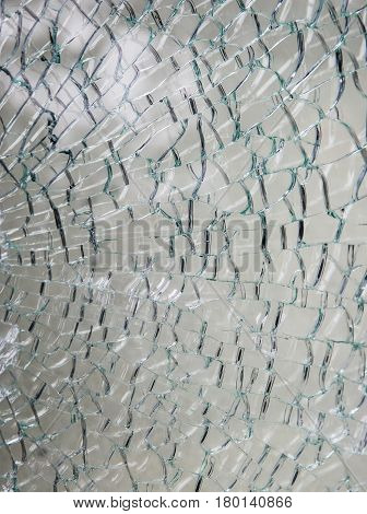 Broken Glass. A pane of safety tempered glass shattered in many pieces.