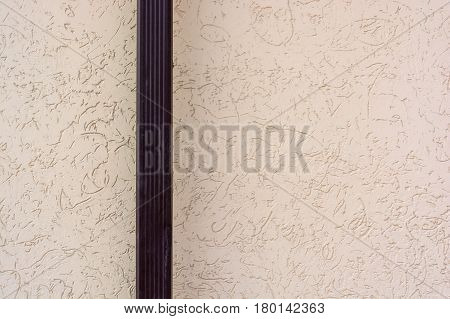 Closeup of brown downspout on beige wall background outdoors