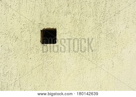 Closeup of black square hole in green wall of modern building abstract background
