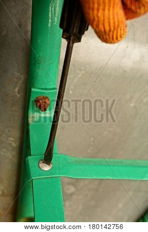Tool screwdriver in hand and old screw on tube and plate