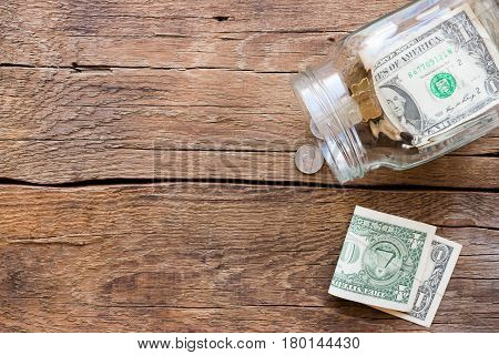 jar for donations with scattered money on wooden background