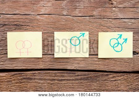 Hand Drawn Gender Symbols On Paper On A Wooden Background