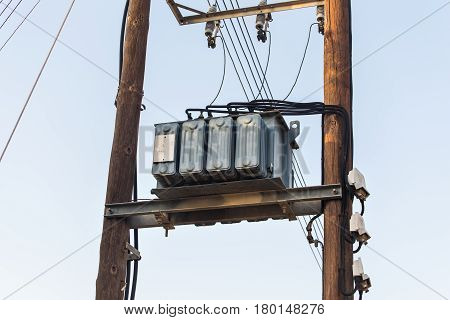Transformers of an electrical post with powerlines against bright blue sky.