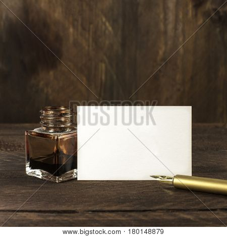 A photo of a blank white thick cardboard business card on a dark wooden background texture with a golden ink pen and ink bottle. A square mockup or a minimalist banner with copy space