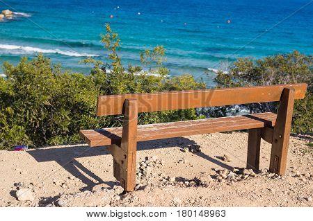 Back view of bench near sea. Sea shore bench