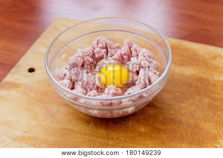 Cooked fresh mince for dish with raw egg lie in a plate