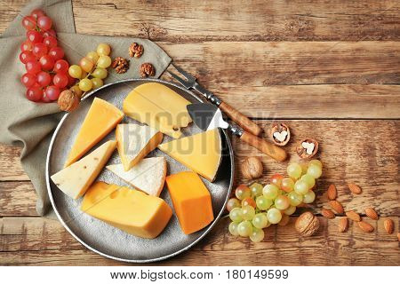 Tray with delicious cheese, grape and nuts on wooden table