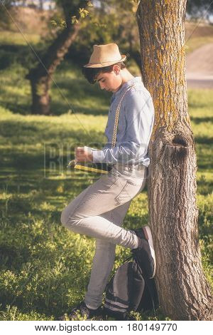 Teenage girl with hat reads placidly down the shade of a tree