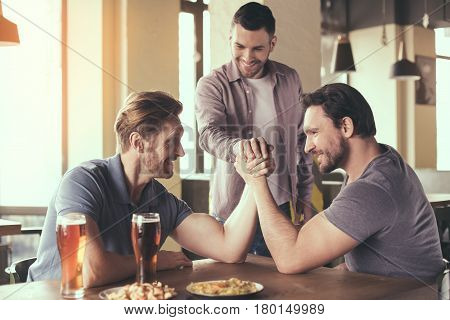 Pizza time. Friends spending time together in restaurant. Guys drinking beer and eating pizza. Men wrestling