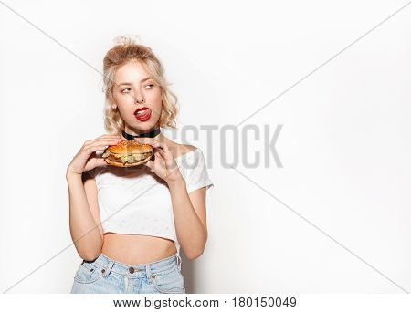 Young woman looking on a side licking her lips and holding a big appetizing burger.