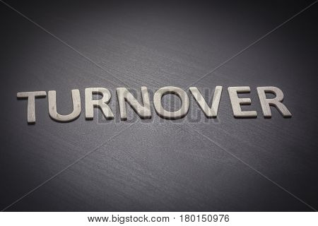 Turnover written with wooden letters on a gray background to understand a concept of economics and finance