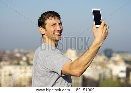 The smiling man is making selfie about himself with phone outdoors on city background.