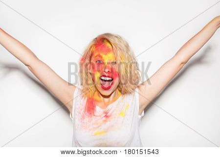 Young expressive cheerful girl with painted face in white t-shirt holding hands up on white background.