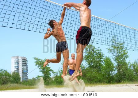 Three Men Playing Beach Volleyball - Two Fight Over Net, Third Watches