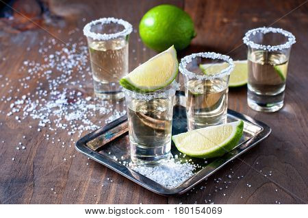 Tequila gold Mexican alcohol in shot glasses lime and salt toned image selective focus