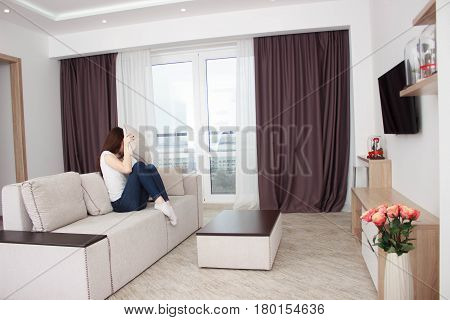 Scared young woman watching tv. Brunette girl sitting on couch With a pillow near the face