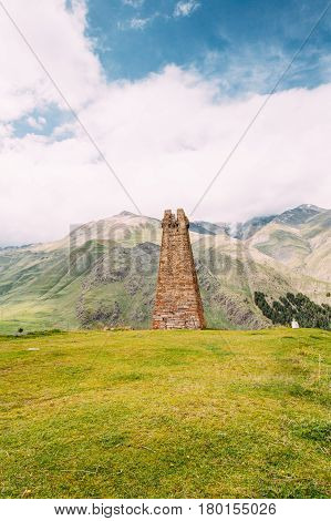 Ancient Old Stone Watchtower On Mountain Background In Sioni Village, Kazbegi District, Mtskheta-Mtianeti Region, Georgia. Spring Or Summer Season. Famous Landmarks And Places In Kazbegi District.