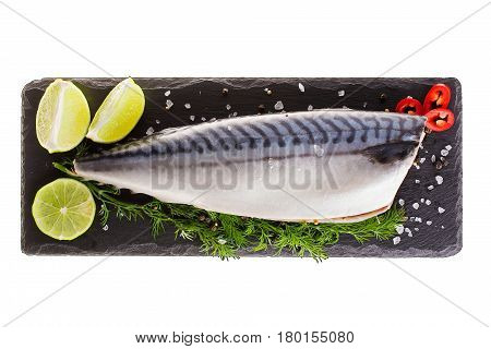 Raw mackerel with lemon and herbs on black slate cutboard isolated on white background. top view