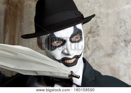 Evil clown wearing a bowler hat holding white umbrella