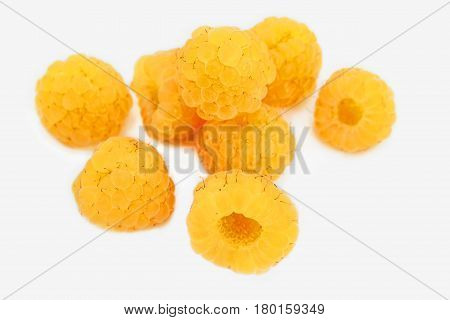 A scattering of a few berries ripe yellow raspberries isolated on a white background