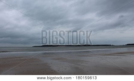 Caldey Island taken from Tenby beach on a cloudy day