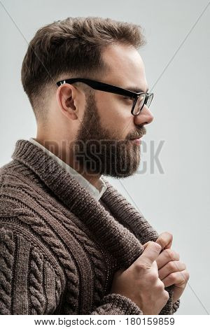 Closeup studio shot of positive young man with beard and glasses holding his cardigan with hands isolated on white