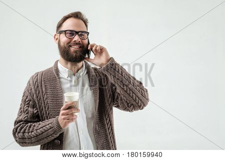 Closeup studio shot of positive hipster with phone and coffee isolated on white