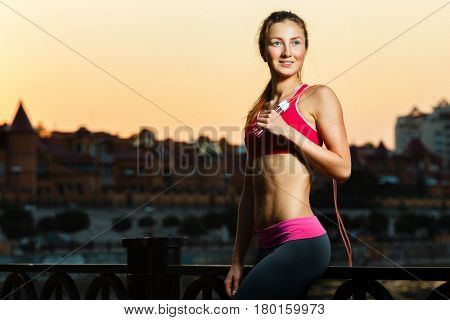 Young female posing with jumping rope on fresh air at sunset
