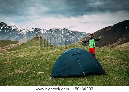 Kazbegi, Georgia - May 22, 2016: Young Tourist Man Is Putting Up A Tent Near Gergeti Trinity Church Or Tsminda Sameba - Holy Trinity Church. Church Is Situated At An Elevation Of 2170 Meters