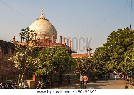 Taj Mahal in sun light with a little indian temple in the front. Early in the morning, back view behind the fence, from outside, street side with a siple indian life. Image with a blue sky. One of the most famous building in the world. This mausoleum was
