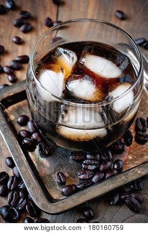 Kahlua liqueur in glasses with coffee beans on a wooden background alcoholic Mexican drink selective focus toned image
