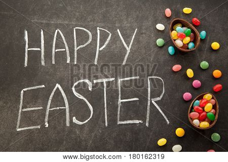 Easter congratulation written by chalk on chalkboard background with chocolate eggs and colorful candies.