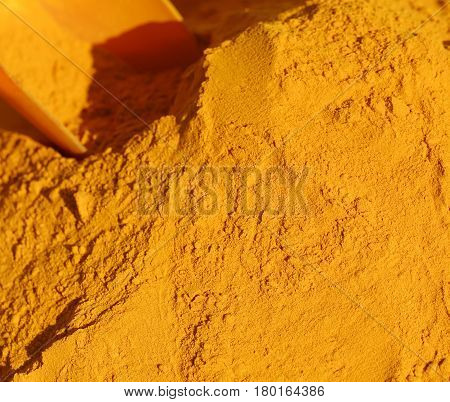 Turmeric Curry Powder Background And A Red Bailer