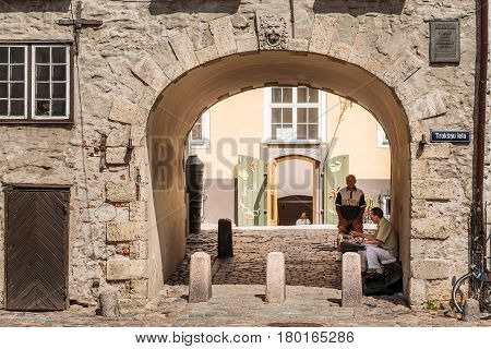 Riga, Latvia - July 1, 2016: Street buskers with keyboard perfoming songs under Arch Of Swedish Gate In Original State On Troksnu Street In Old Town. Cultural Monument, Part Of Ancient Architectural Historical Complex.