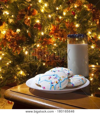 Sweet cookied and milk next to a Christmas tree waiting for Santa