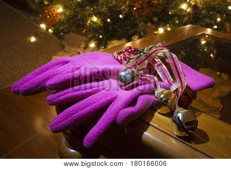 Bright pink gloves on a table with a Christmas tree behind
