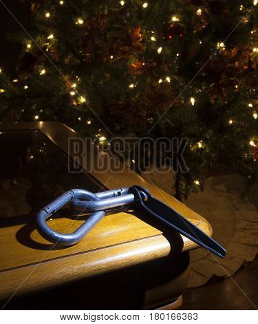 Pair of carabiners and a piton near a lit Christmas tree