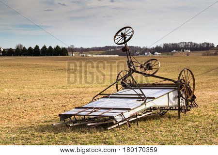 Amish farm hay bind harvesting implement lying in a field