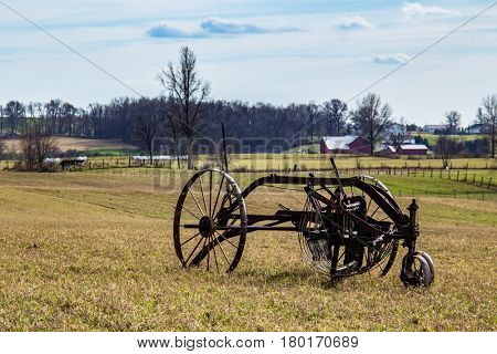 Amish harvesting implement laying in a field.