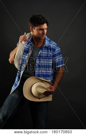 The cowboy is holding his hat and lasso.