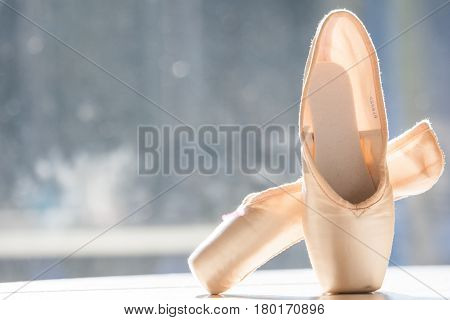 A pair of ballet shoes pointes standing in the sunlight against a window.