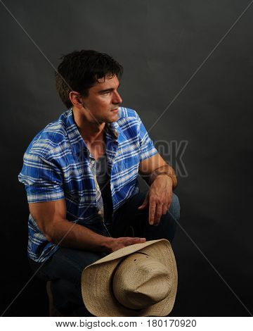 The attractive cowboy sits and waits for his love.
