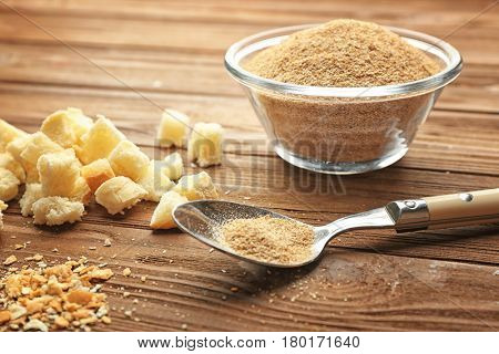 Glass bowl of bread crumbs and croutons on wooden background