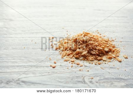 Heap of wheaten breadcrumbs on wooden table