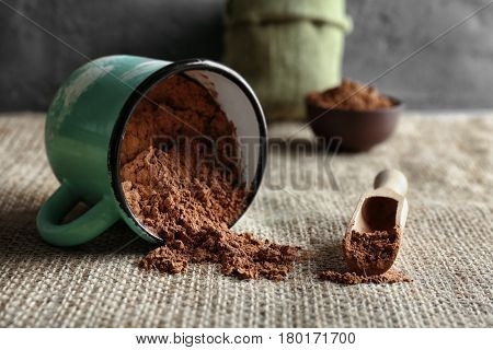 Wooden scoop and metal mug with cocoa powder on kitchen table