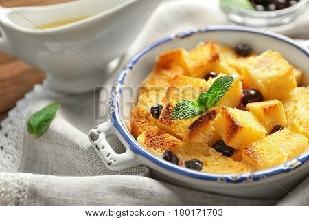 Bowl with delicious bread pudding on napkin