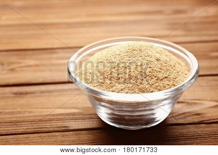 Glass bowl of breadcrumbs on wooden table