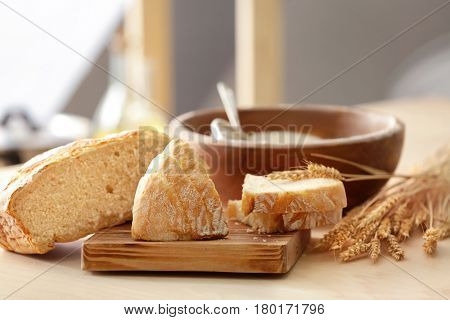 Tasty bread, wheat spikelets and wooden board on kitchen table
