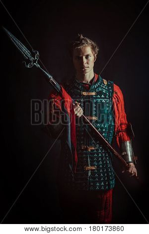 Young Medieval Warrior With The Spear. Dark Background.