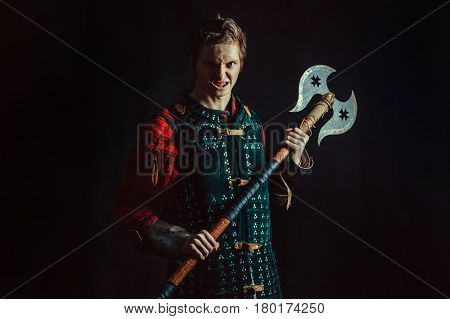Young Medieval Warrior With The Axe. Dark Background.